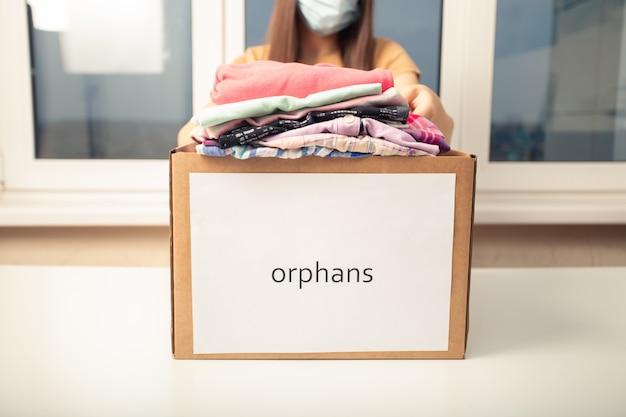 Una giovane donna in una fondazione di beneficenza tiene una scatola di vestiti per gli orfani