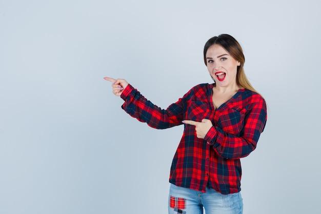 Giovane donna in camicia a quadri che punta a sinistra e sembra felice, vista frontale.