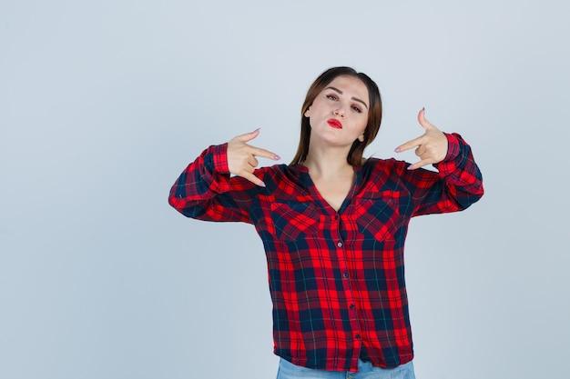Giovane donna in camicia a quadri che mostra gesto rock e sembra sicura, vista frontale.