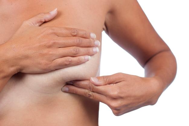 Giovane donna che controlla il seno (autoesame automatico) per anomalie, nodi o strani noduli per cancro al seno.
