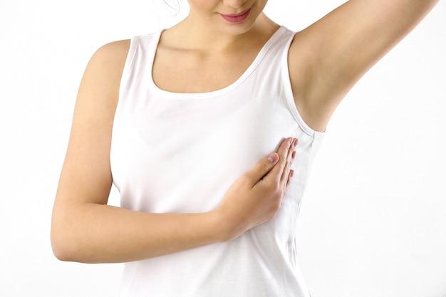 Giovane donna che controlla il suo seno su fondo bianco. concetto di consapevolezza del cancro