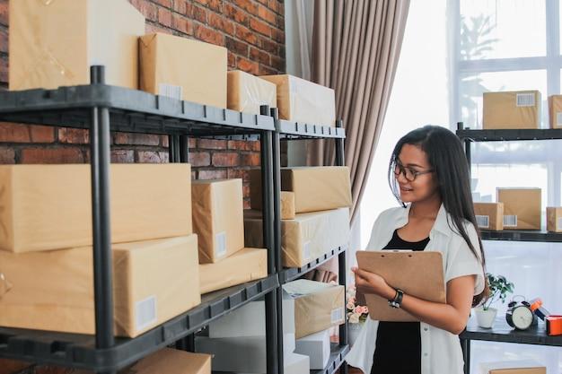 Giovane donna che controlla i pacchetti con la lavagna per appunti