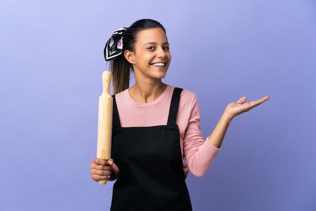 Giovane donna in uniforme da chef che estende le mani di lato per invitare a venire