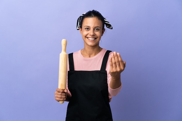 Giovane donna in uniforme del cuoco unico che invita a venire con la mano. felice che tu sia venuto