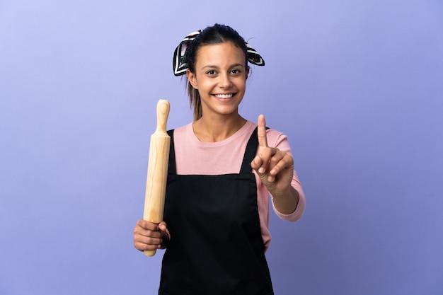 Giovane donna in uniforme del cuoco unico che mostra e che alza un dito