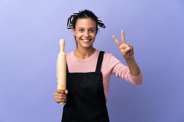 Giovane donna in uniforme del cuoco unico che sorride e che mostra il segno di vittoria