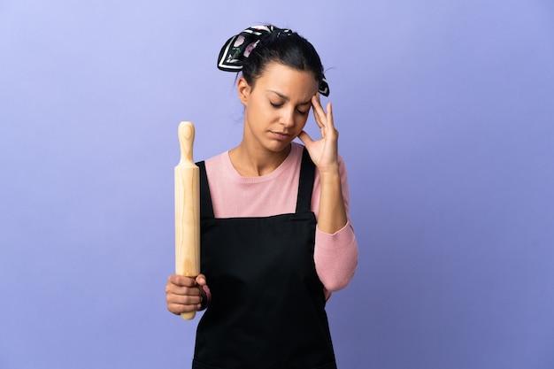 Giovane donna in uniforme da chef con mal di testa
