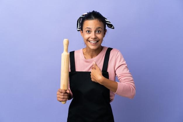 Giovane donna in uniforme da chef con espressione facciale a sorpresa