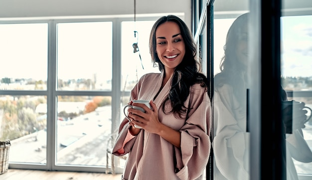 Giovane donna agghiacciante a casa sullo sfondo di una finestra e una sedia pensile con una tazza di caffè in mano. ragazza che si distende nel soggiorno indossando accappatoio a casa.