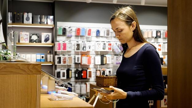 La giovane donna sceglie un nuovo smartphone in un negozio di elettronica. il cliente femminile sta tenendo due telefoni intelligenti e lo sta confrontando.