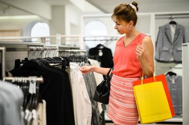 Giovane donna che sceglie i vestiti su uno scaffale in uno showroom