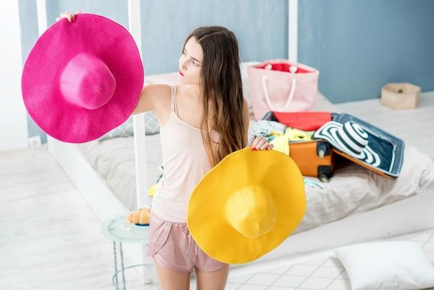 Giovane donna che sceglie cappello in camera da letto con valigia e vestiti sullo sfondo. preparativi per le vacanze estive
