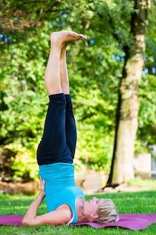 Giovane donna nel parco cittadino che fa yoga o in fase di riscaldamento per l'esercizio