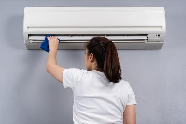 Giovane donna che pulisce il condizionatore d'aria con un panno a casa