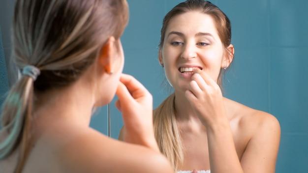 Giovane donna che pulisce e controlla i denti allo specchio in bagno.