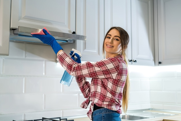 Giovane donna pulizia cappa da cucina con straccio e detersivo in cucina. concetto di pulizie