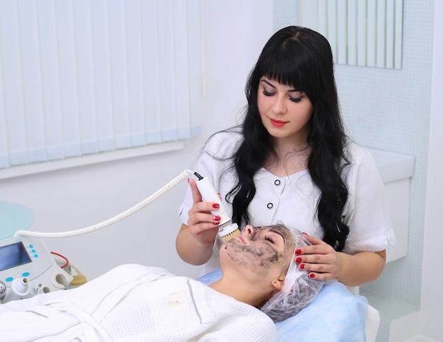 Giovane donna che pulisce la pelle con un pennello a un cliente