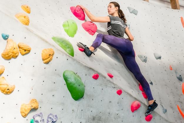 Giovane donna arrampicata su masso artificiale