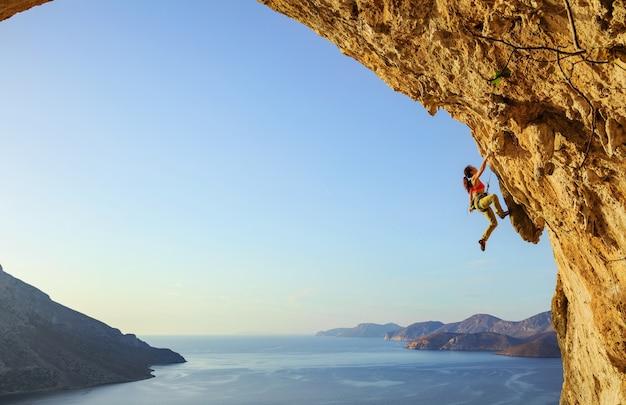 Giovane donna arrampicata percorso impegnativo in grotta al tramonto, kalymnos island, grecia