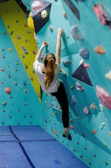 Giovane donna che si arrampica sul muro di allenamento in palestra