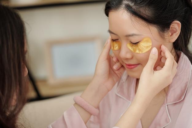 Giovane donna che chiude gli occhi quando un'amica l'aiuta ad applicare i cerotti in gel per gli occhi