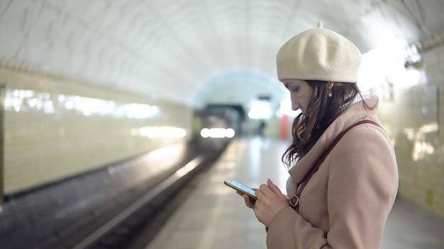 Giovane donna in cappotto con telefono in metropilitene in attesa di un treno.