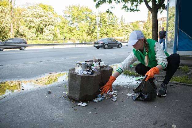 Giovane donna che raccoglie spazzatura per le strade della città, copia spazio