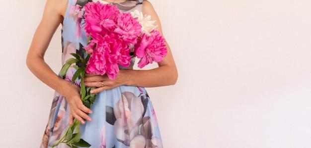 Una giovane donna in un vestito colorato con un mazzo di fiori di peonia nelle sue mani su uno sfondo rosa chiaro con uno spazio di copia
