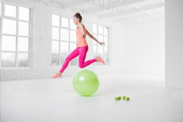 Giovane donna in abbigliamento sportivo colorato che salta sopra la palla fitness nella stanza bianca con grandi finestre