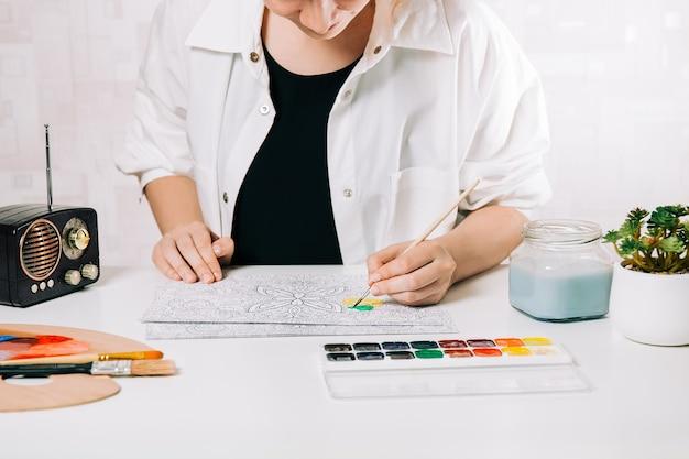 Giovane donna da colorare antistress a tavola al chiuso, benessere mentale e arteterapia. la donna dipinge uno schizzo con il pennello, processo meditativo di pagine da colorare. espressione di sé per arte