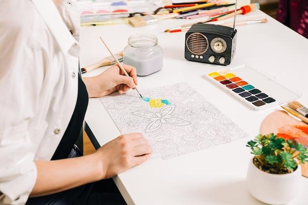 Giovane donna da colorare antistress a tavola al chiuso, benessere mentale e arteterapia. la donna dipinge uno schizzo, processo meditativo di pagine da colorare. espressione di sé per arte