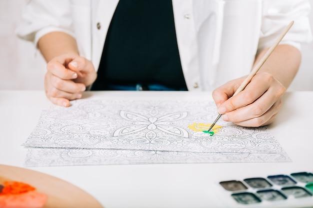 Giovane donna da colorare antistress a tavola al chiuso, benessere mentale e arteterapia. la donna dipinge uno schizzo, processo meditativo di pagine da colorare