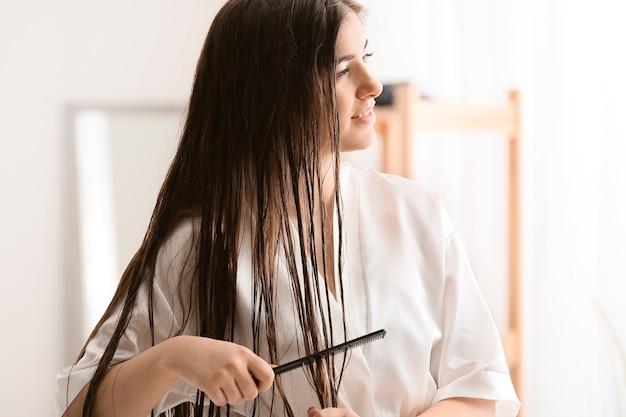Giovane donna che pettina bei capelli lunghi in bagno