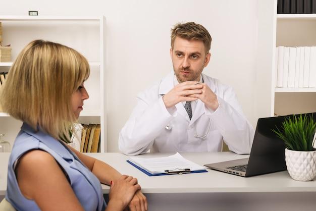 Giovane donna su una consultazione con un chirurgo o un terapista maschio nel suo ufficio. messa a fuoco selettiva sul medico.