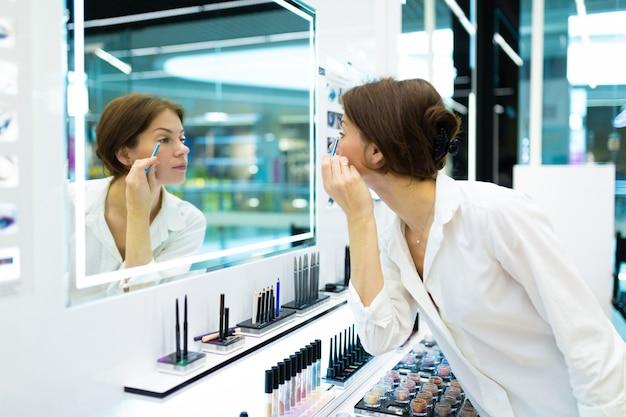 La giovane donna nel negozio di cosmetici sta truccando con la matita blu davanti allo specchio
