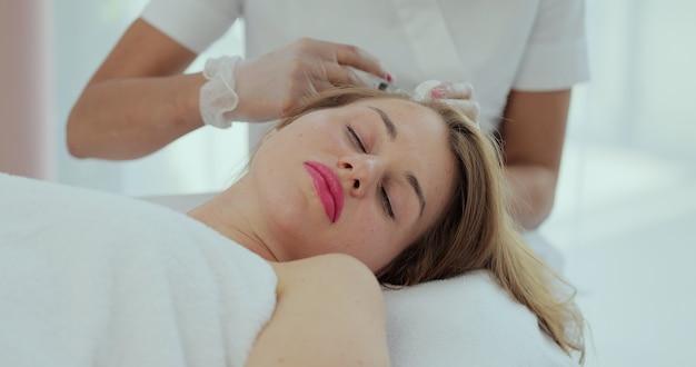 Giovane donna nel gabinetto di cosmetologia. la donna riceve un'iniezione nella testa. il concetto di mesoterapia.