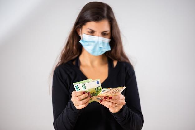 Giovane donna che conta soldi e che indossa la maschera per il viso durante la pandemia