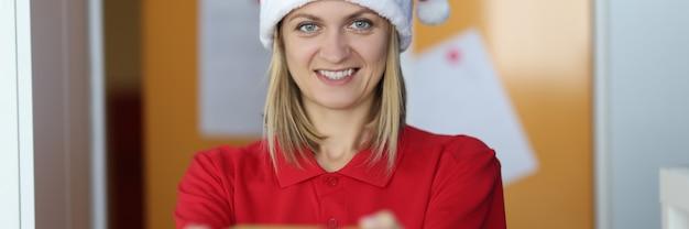 Il corriere della giovane donna in cappello di babbo natale tiene la scatola con il regalo nelle sue mani