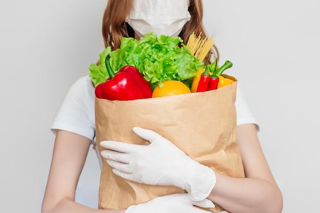 Il volontario del corriere della giovane donna che indossa una maschera medica tiene un sacco di carta con prodotti, verdure, peperoncino rosso, erbe isolate sopra spazio bianco e grigio, concetto di consegna del cibo
