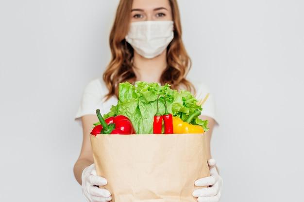 Il volontario del corriere della giovane donna che indossa una maschera medica tiene un sacco di carta con le verdure isolate, consegna sicura dell'alimento