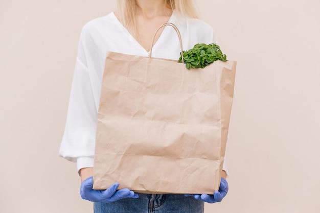 Il volontario del corriere della giovane donna che indossa una maschera protettiva tiene un sacchetto di carta con i prodotti