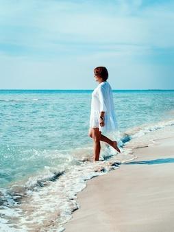 Giovane donna in cover up gioca con le onde del mare sulla spiaggia. concetto di viaggi e vacanze.