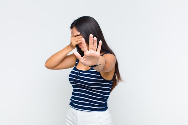 Giovane donna che copre il viso con la mano e mette l'altra mano davanti per fermare la fotocamera, rifiutando foto o immagini