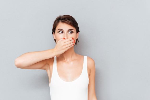 Giovane donna che copre la bocca con il palmo isolato su uno sfondo grigio