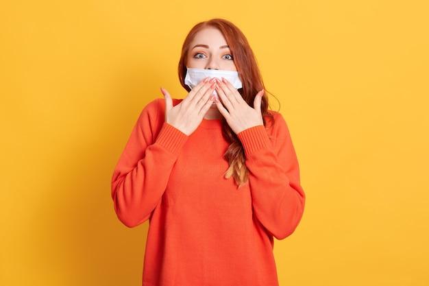 Giovane donna che copre la bocca con la mano, sembra scioccata dalla vergogna per l'errore