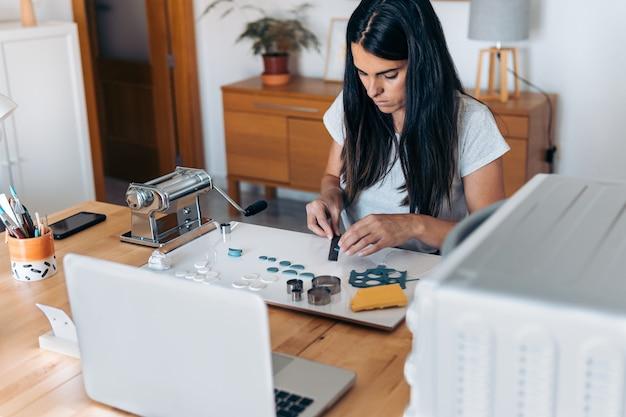 Giovane donna che crea gioielli fatti a mano usando l'argilla e lavorando da casa.