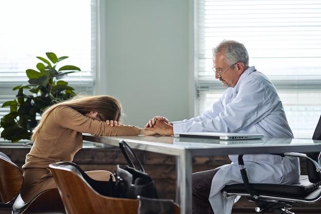Una giovane donna piange sentendo una diagnosi sfavorevole all'appuntamento di un medico