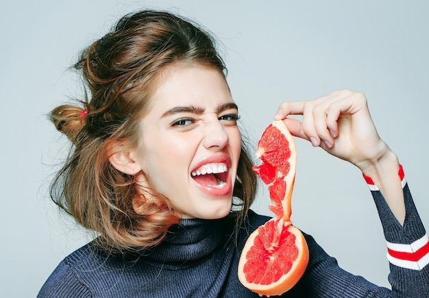 La giovane donna o la ragazza sexy sveglia tiene il succo di estate fresco della fetta della frutta del pompelmo