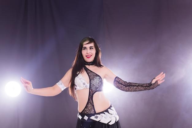 Giovane donna che balla in stile tribal fusion. danza del ventre sul palco.