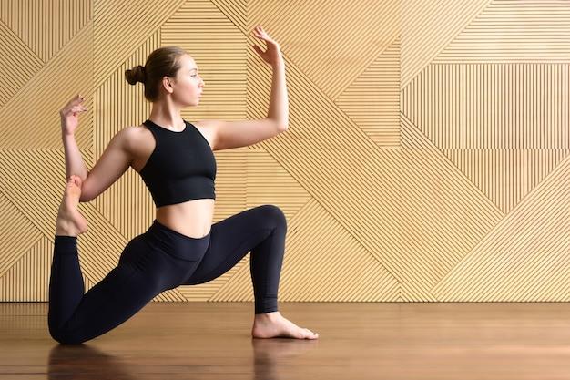 La giovane donna in abbigliamento sportivo scuro dimostra l'esercizio del cavaliere del cavallo. la ragazza pratica lo yoga sullo sfondo di un muro con un motivo poligonale.